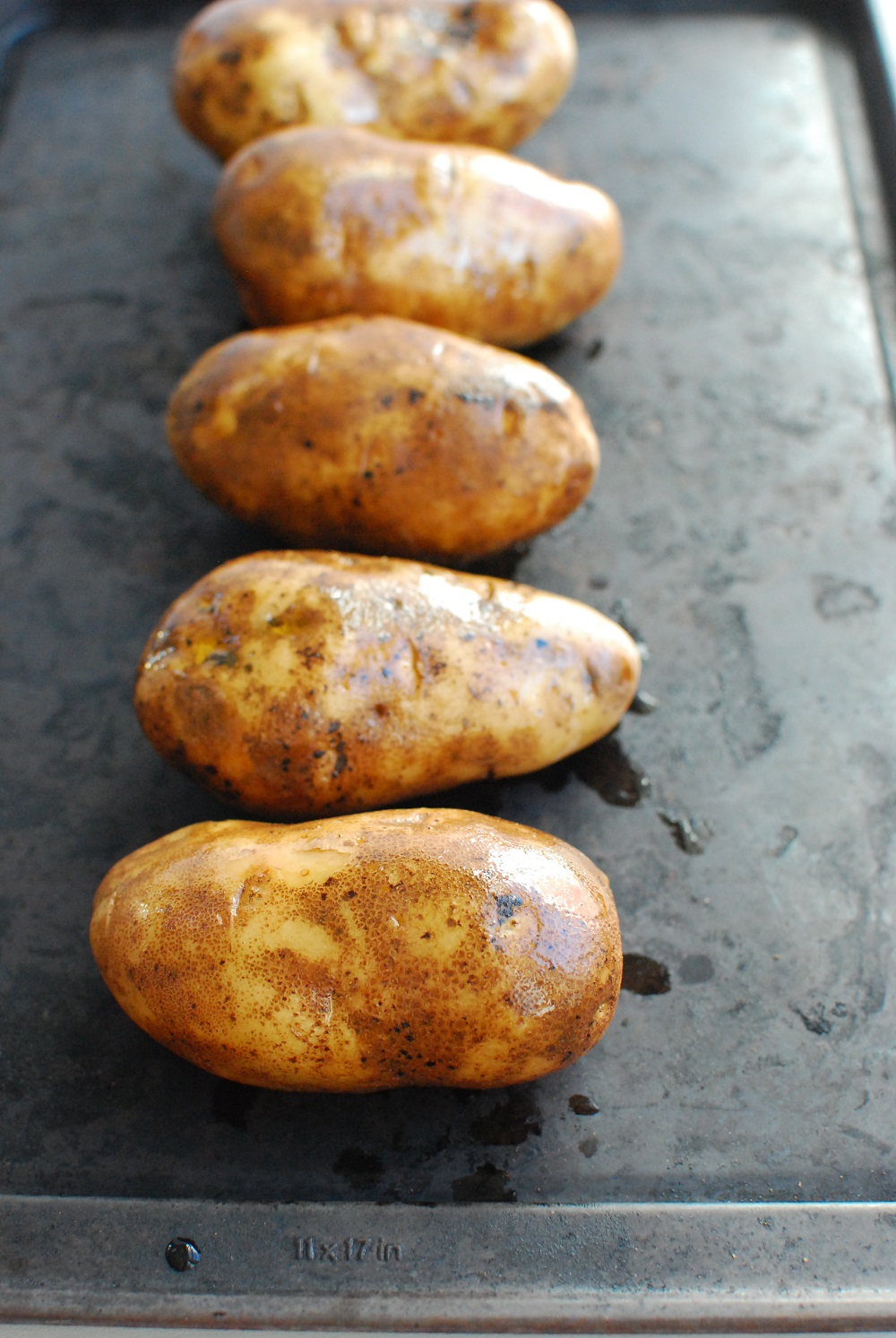 several potatoes on a baking sheet