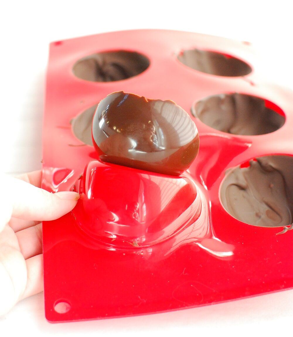 a woman popping chocolate out of a silicone dome mold