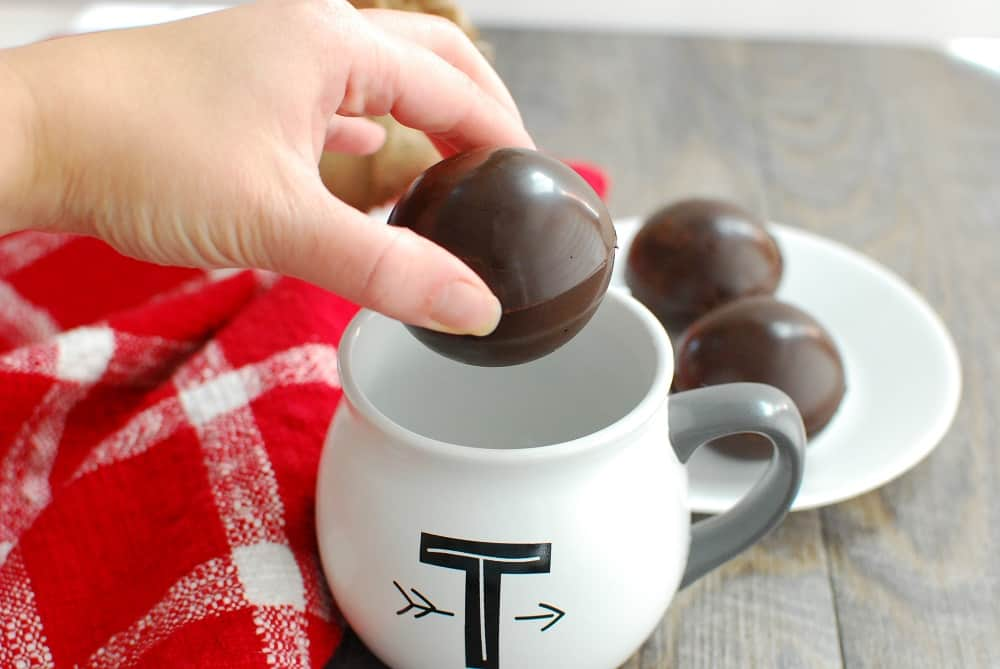 a woman's hand about to drop a dairy free hot chocolate bomb in a mug