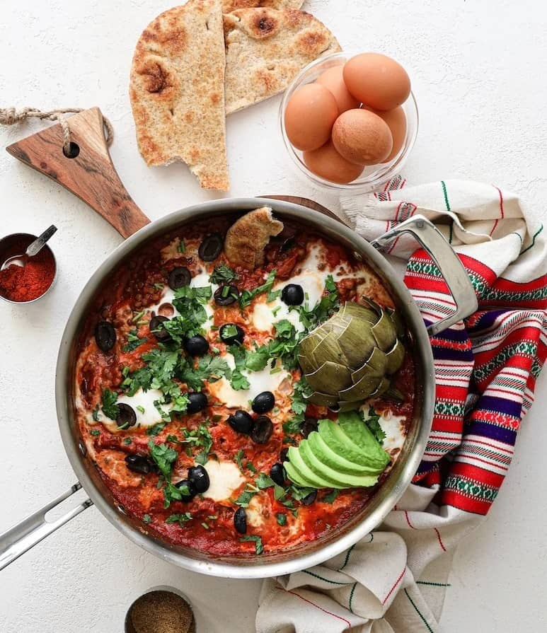 shakshuka in a skillet next to some eggs and flatbread