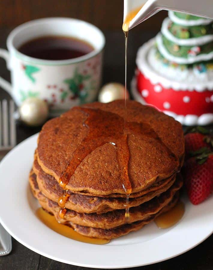 a stack of dairy free gingerbread pancakes with syrup being poured on top