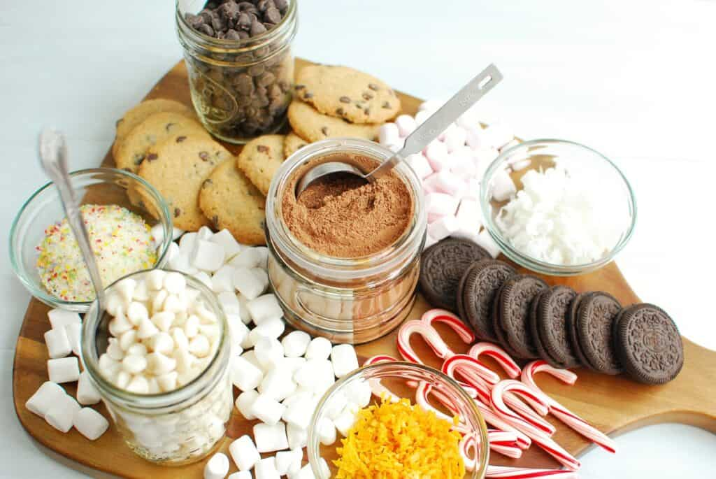 a dairy free hot cocoa charcuterie board with chocolate chips, candy canes, and other ingredients