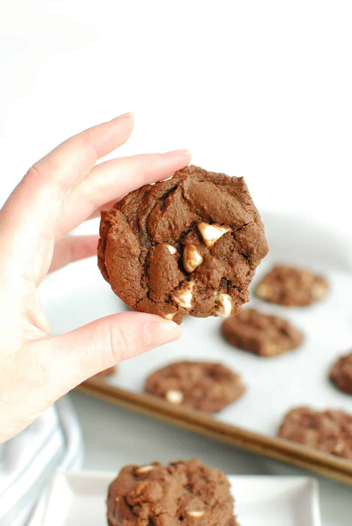 a woman's hand holding a dairy free chocolate cookie with white chocolate chips