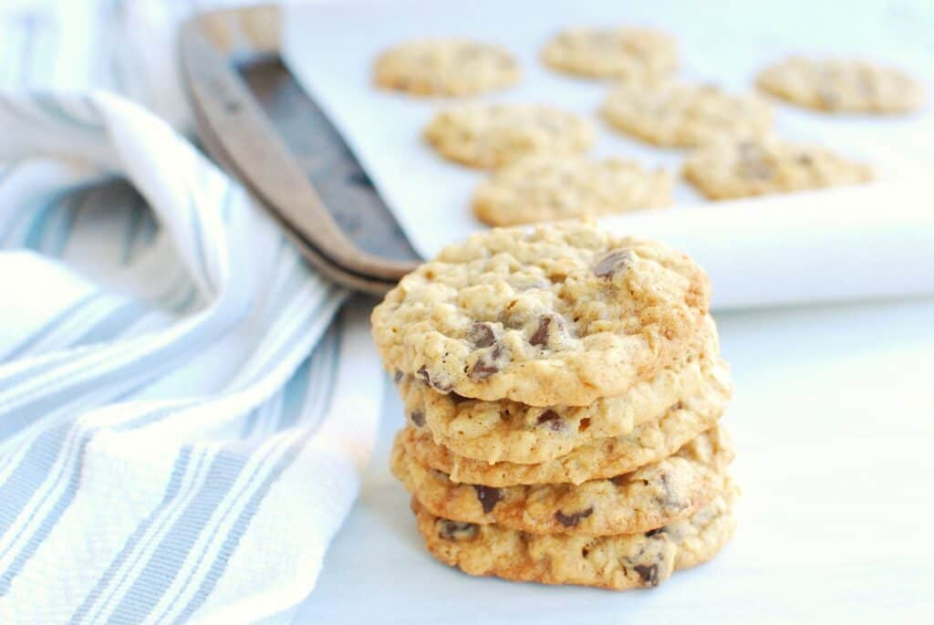 Several dairy free oatmeal cookies stacked on top of each other next to a napkin and a baking sheet.