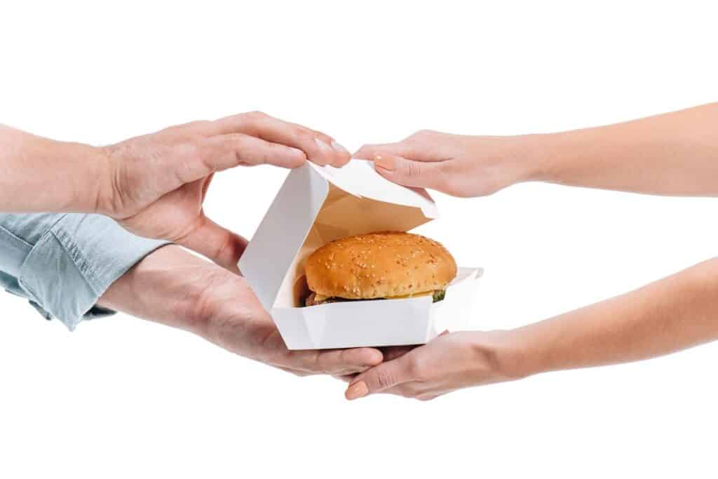 a woman taking a dairy free takeout burger from a man's hands