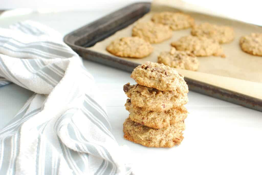 Several tahini oatmeal cookies next to a napkin and a baking sheet.