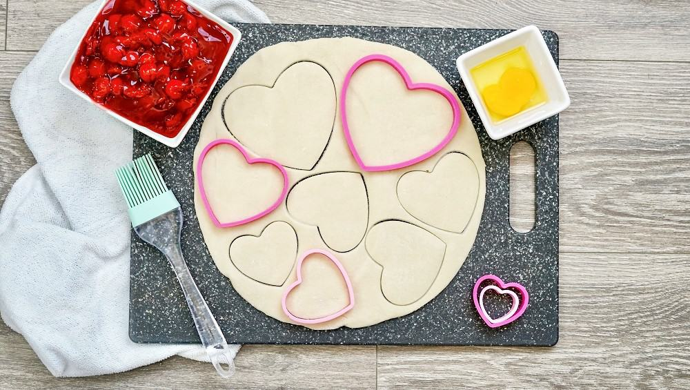 Pie crust on a cutting board with heart shaped cookie cutters.