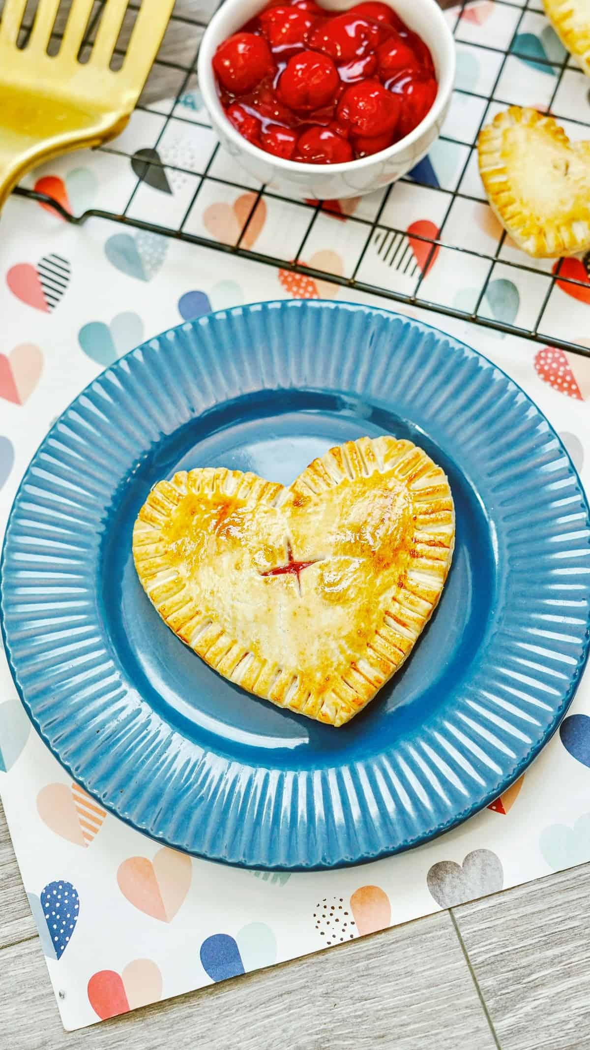 An air fryer hand pie on a blue plate next to a bowl of cherry pie filling and a spatula.