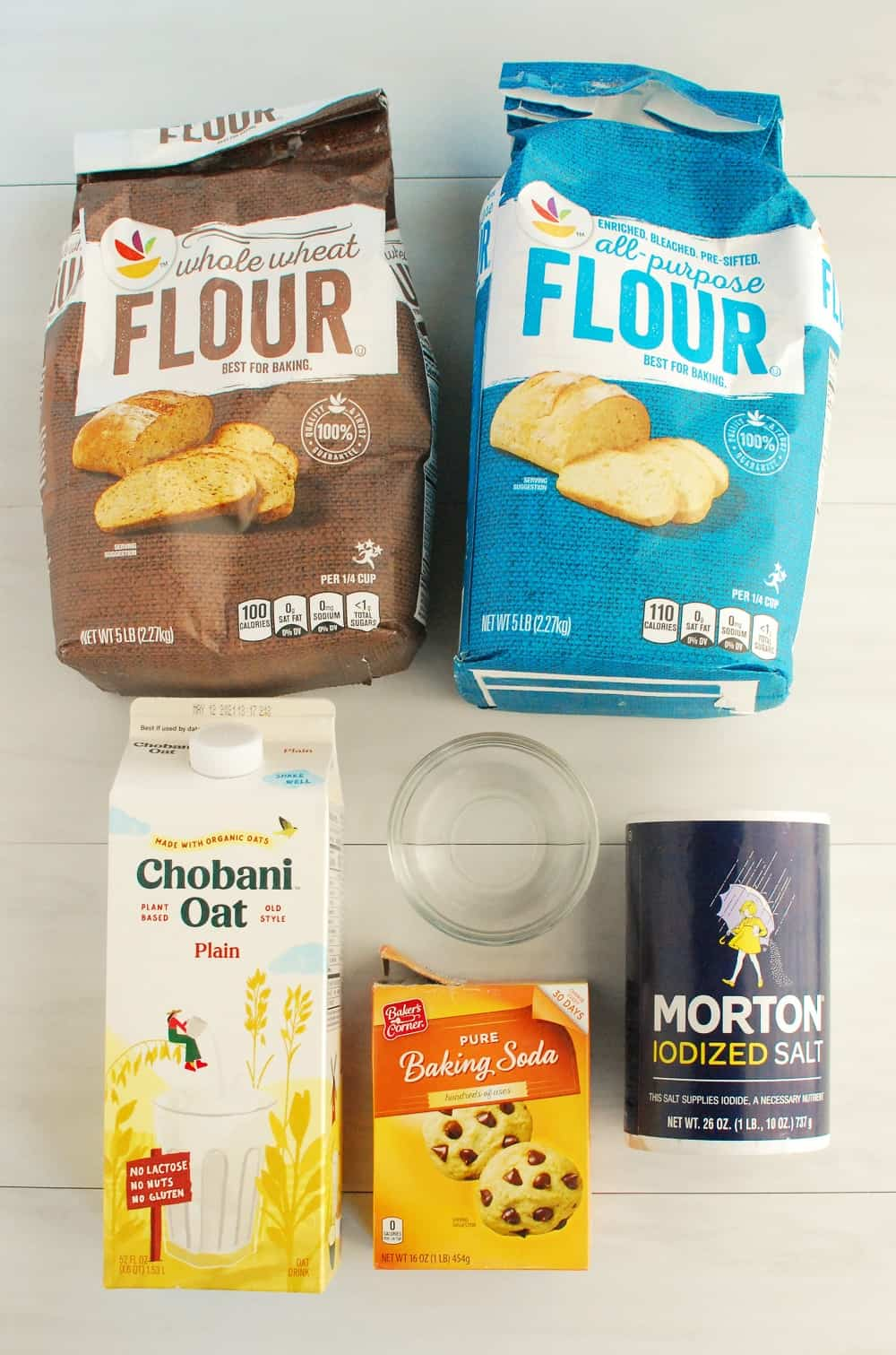 A package of whole wheat flour, a package of white flour, a carton of oat milk, a box of baking soda, a canister of salt, and a small bowl with vinegar.