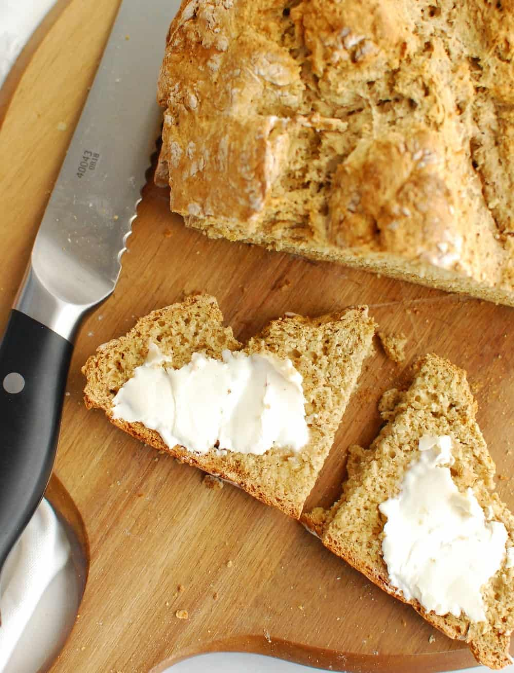 A slice of Irish soda bread with dairy free butter slathered on top.