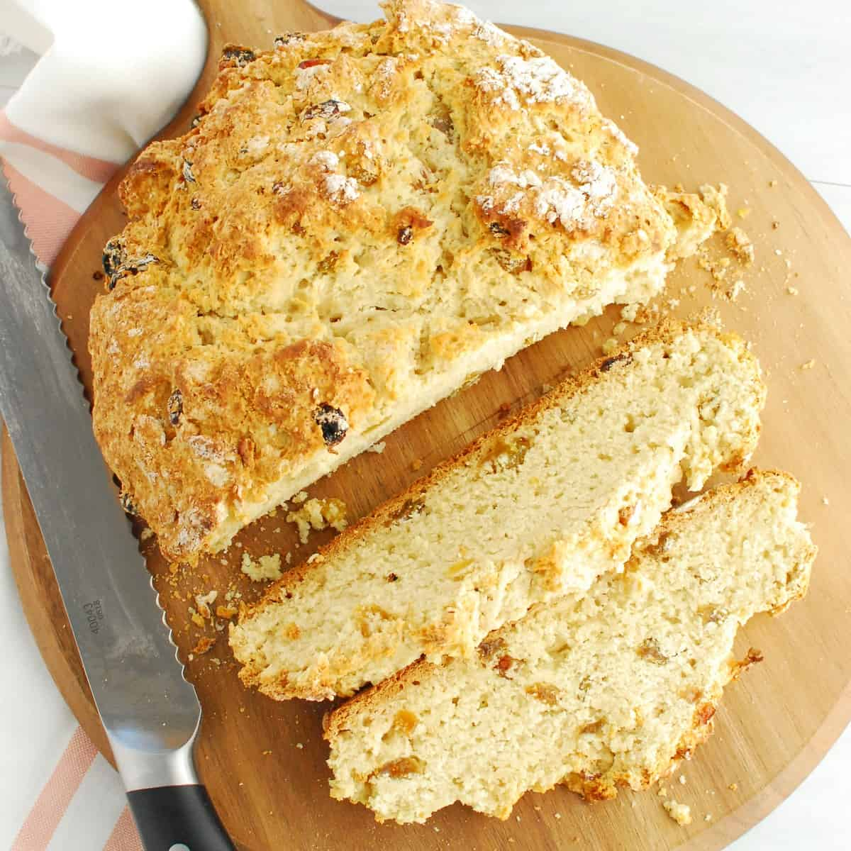 A loaf of sweetened vegan Irish soda bread with raisins with two slices cut from it.