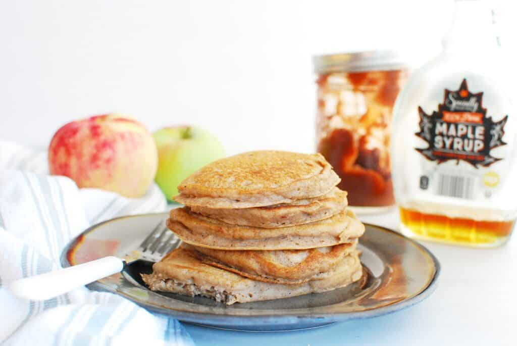 Several apple pancakes on a plate next to a jar of apple butter and a bottle of maple syrup.