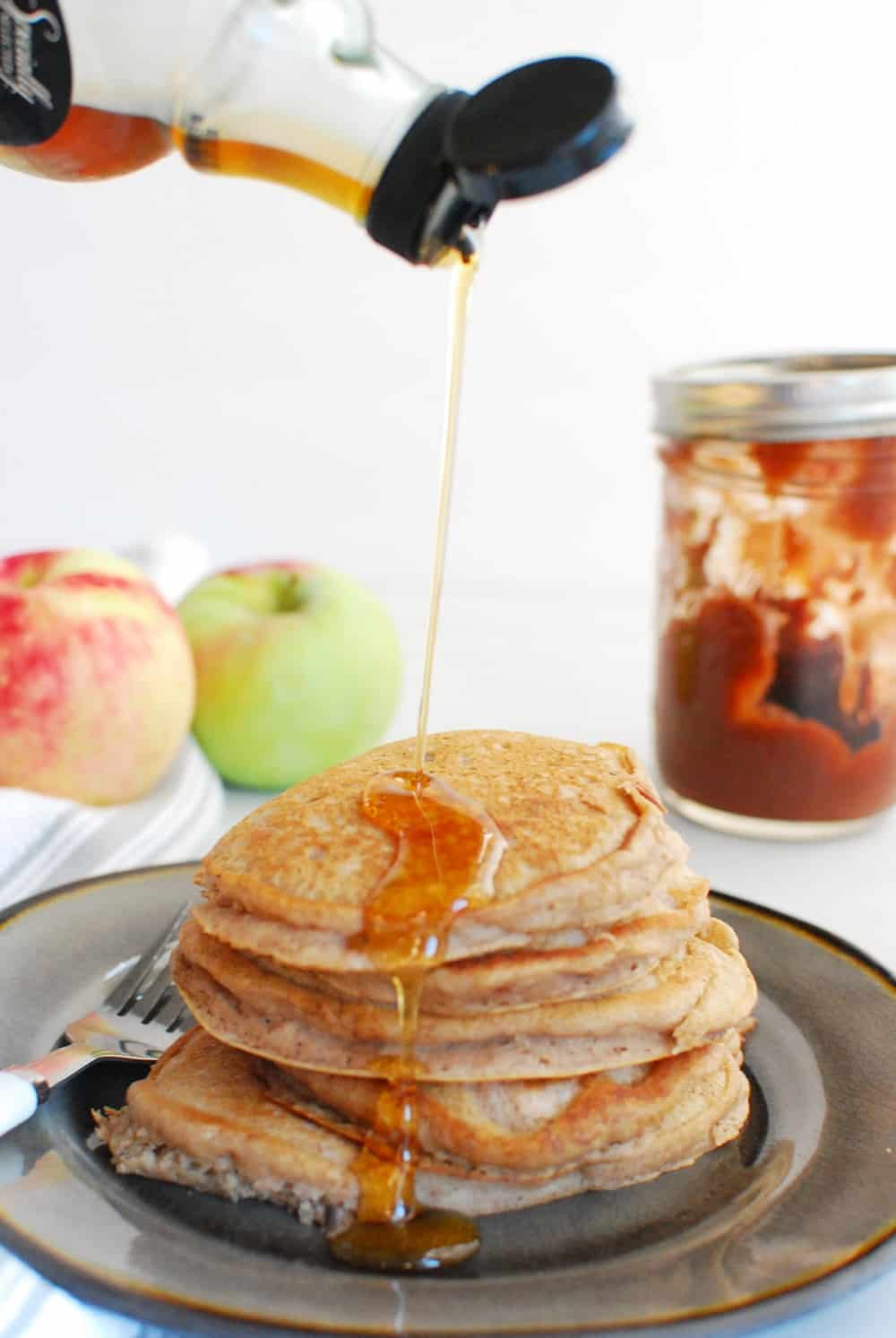 Drizzling pure maple syrup onto a stack of pancakes.