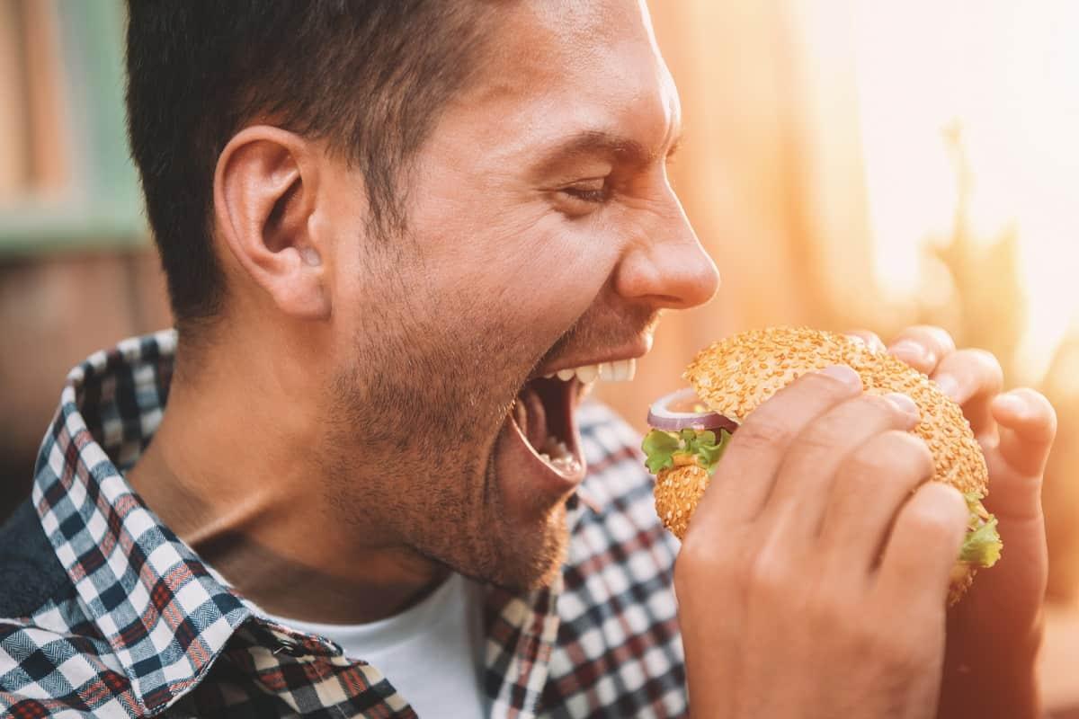 A man eating a dairy free hamburger.
