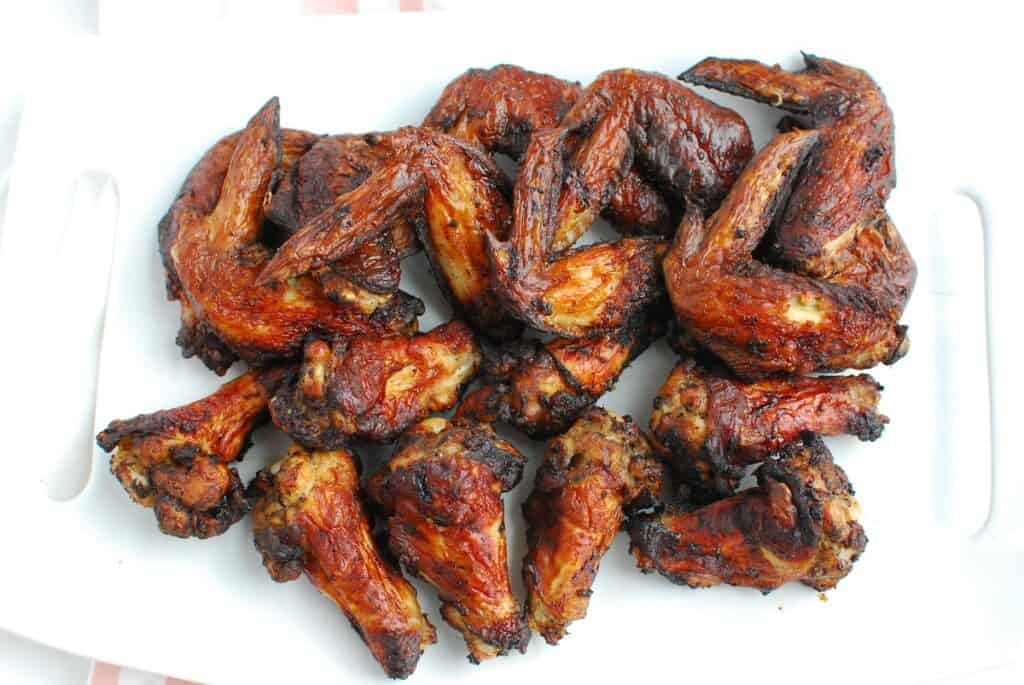 A white platter full of air fryer jerk chicken wings.