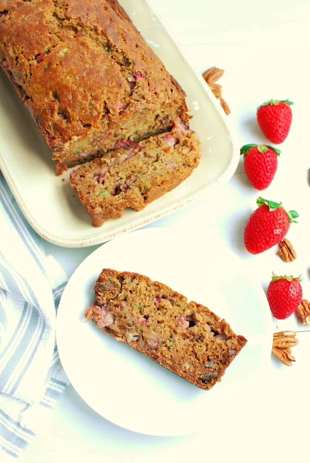A slice of strawberry zucchini bread on a white plate next to the loaf and some fresh strawberries.