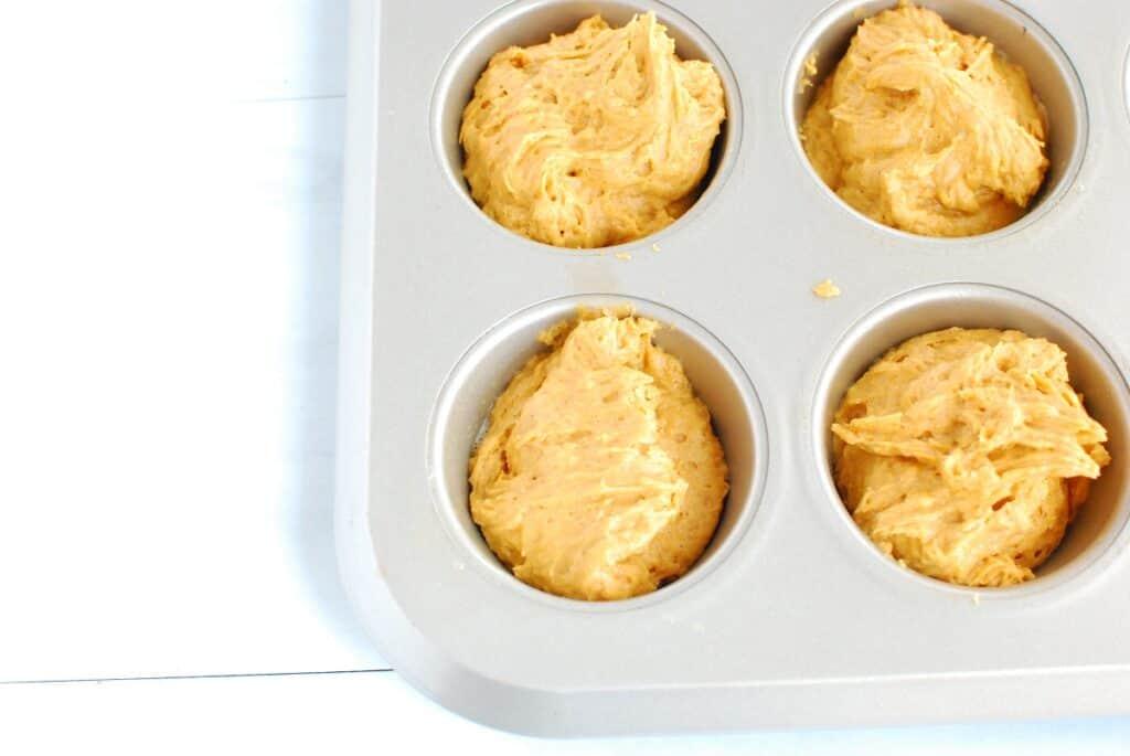 Pumpkin muffin batter poured into a muffin tin.