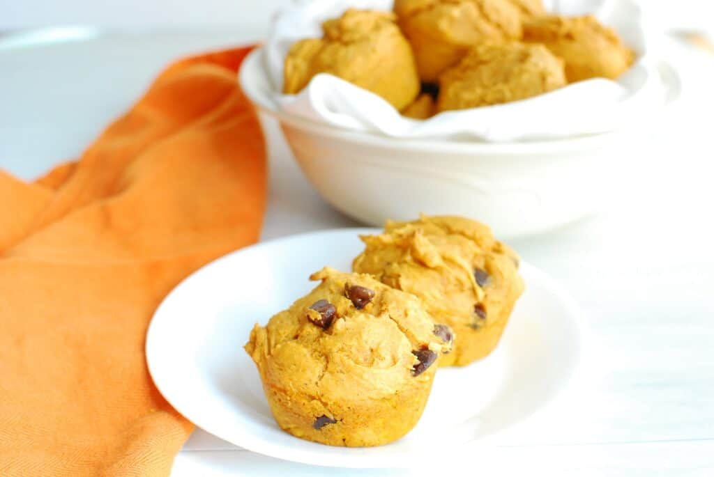 Pumpkin muffins with chocolate chips on a plate next to an orange napkin.