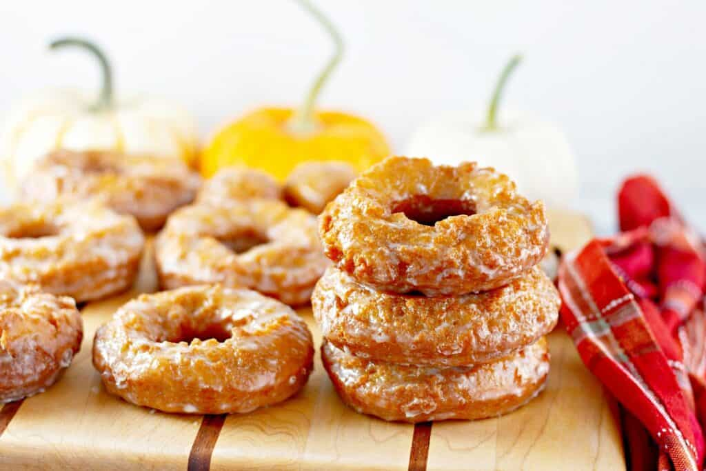 3 dairy free pumpkin donuts stacked on top of each other next to more glazed donuts.