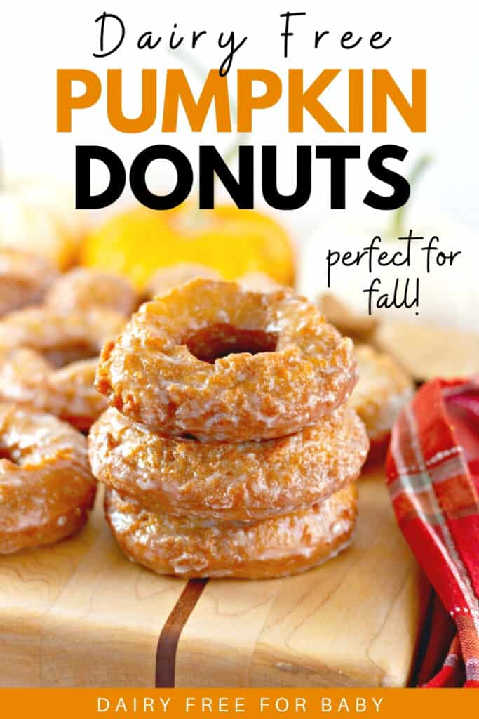 A stack of three dairy free pumpkin donuts on a wooden cutting board.
