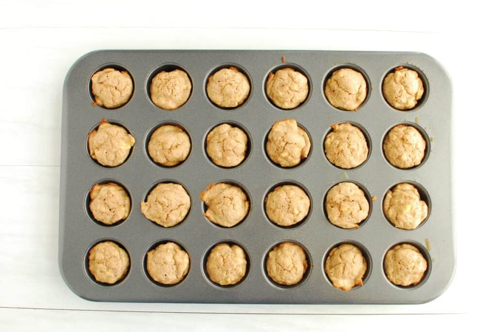 A baked tray of mini baby banana muffins.