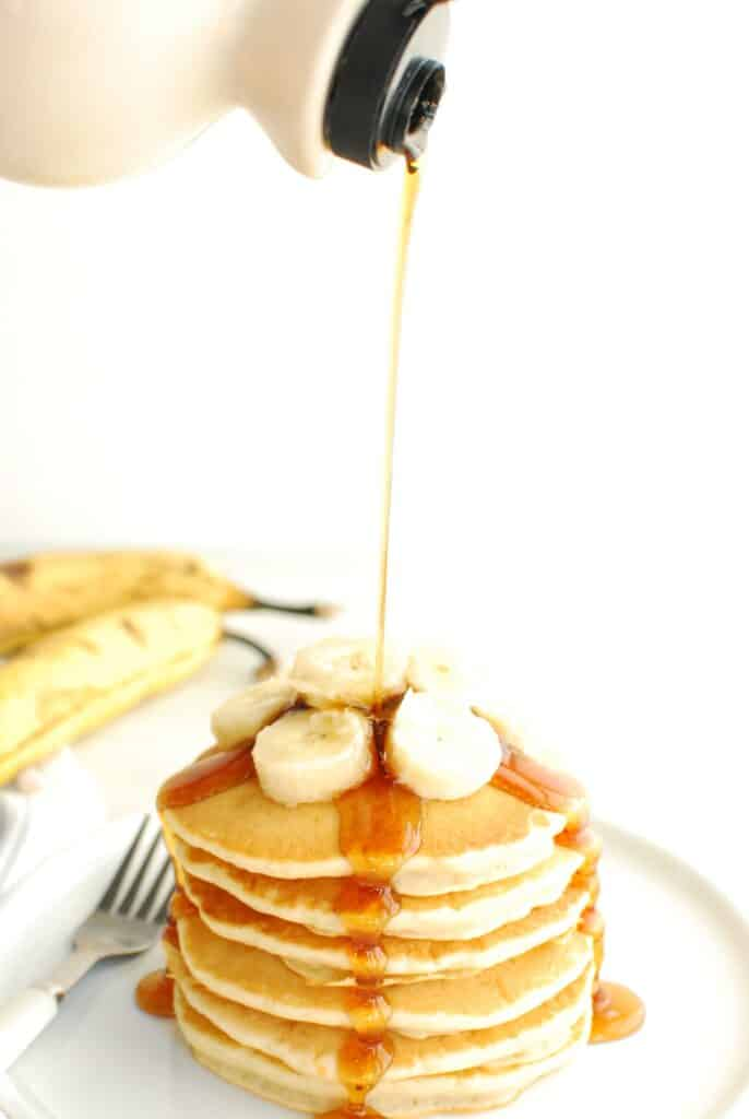 A bottle of maple syrup being poured on a stack of dairy free banana pancakes.