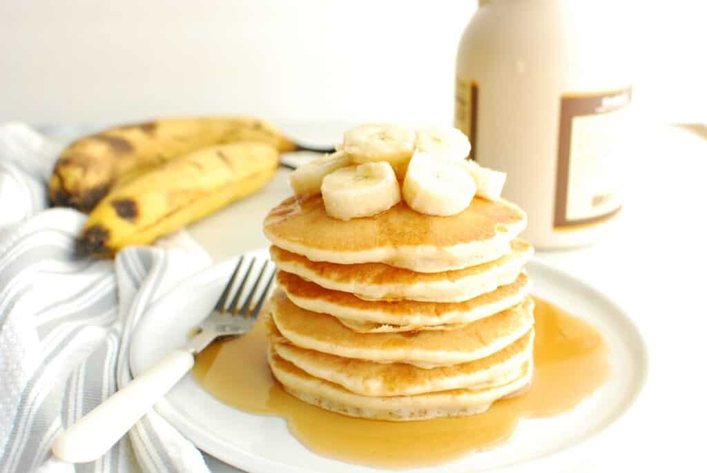 A stack of dairy free banana pancakes on a plate topped with sliced bananas.