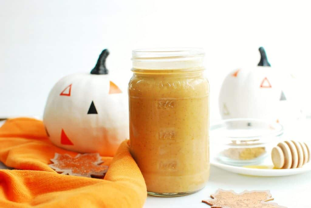 A jar of dairy free pumpkin spice creamer next to an orange napkin and a decorative pumpkin.