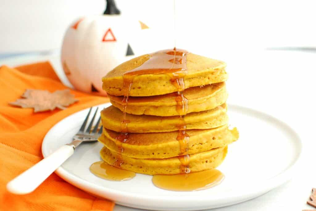 A stack of dairy free pumpkin pancakes on a white plate next to an orange napkin and a decorative pumpkin.